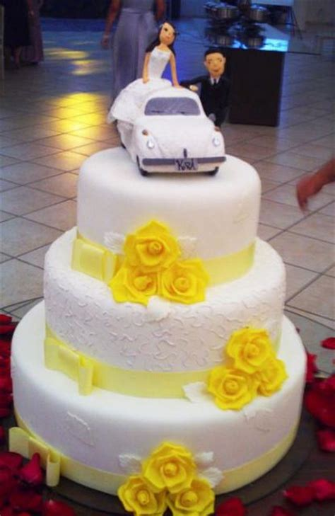 Three tier white round wedding cake with yellow roses and